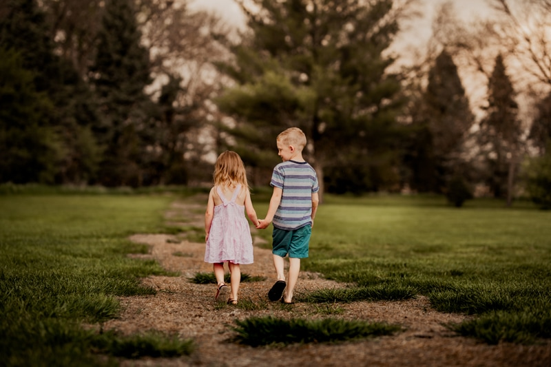Family Photography, a young girl and boy, brother and sister, hold hands on a nature trail