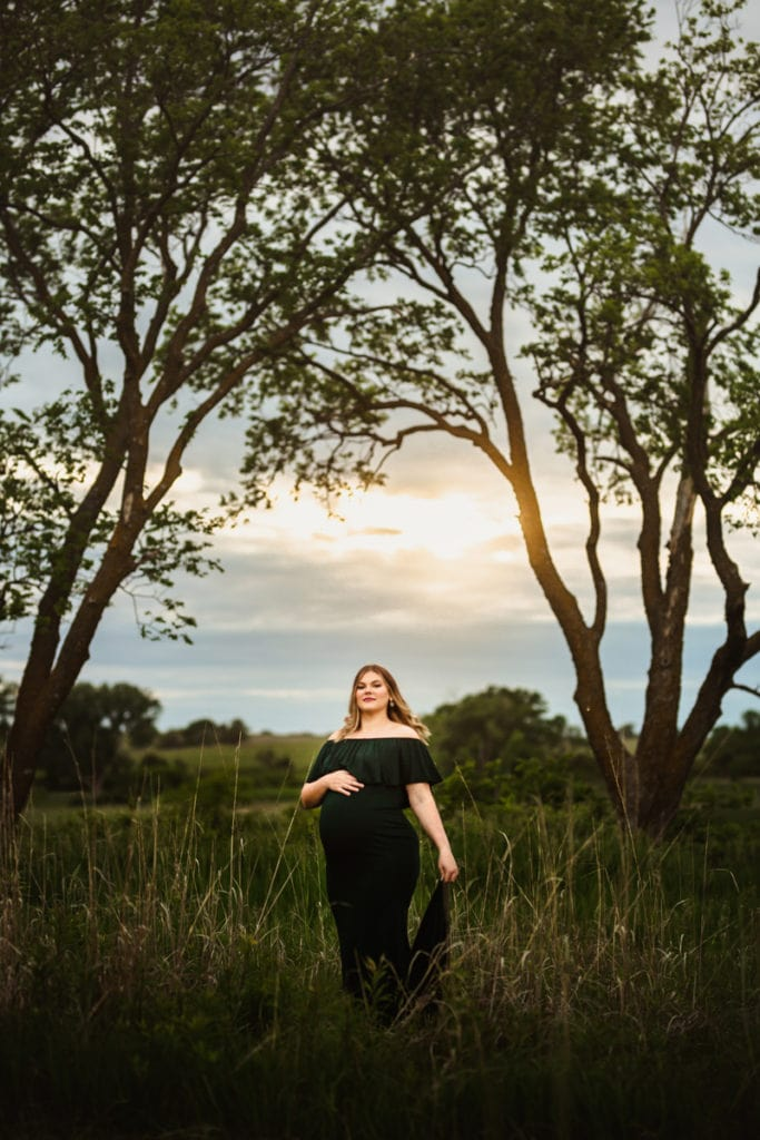 Maternity Photographer, a woman in a green dress holds her pregnant belly beneath the trees