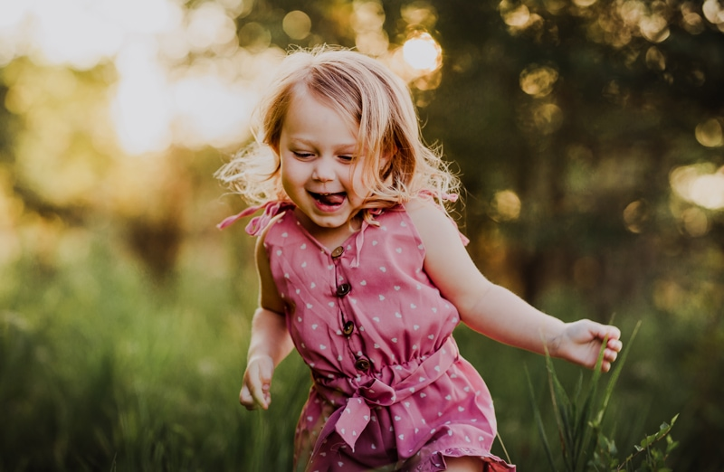 Family Photographer, a young girl smiles and runs through the grass