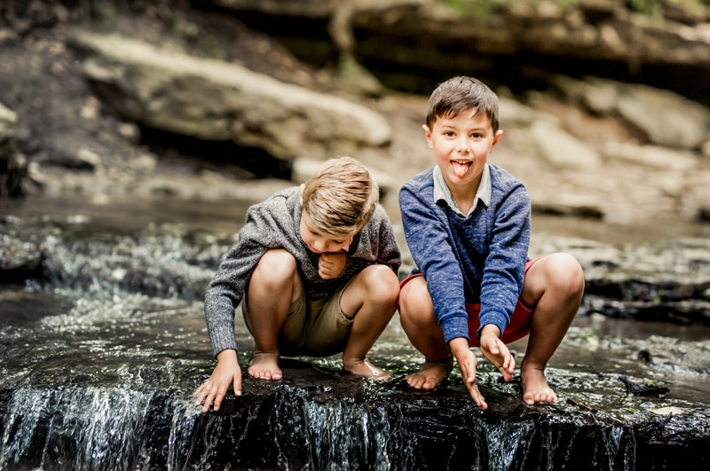 Family Photographer, two brothers sit above a small waterfall in the river