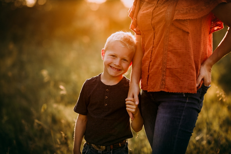 Family Photographer, a little boy holds his mothers hand outdoors