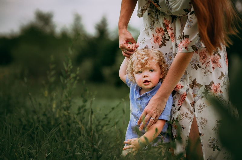 Family Photographer, a little toddler boy holds his mom's hand in a grassy field
