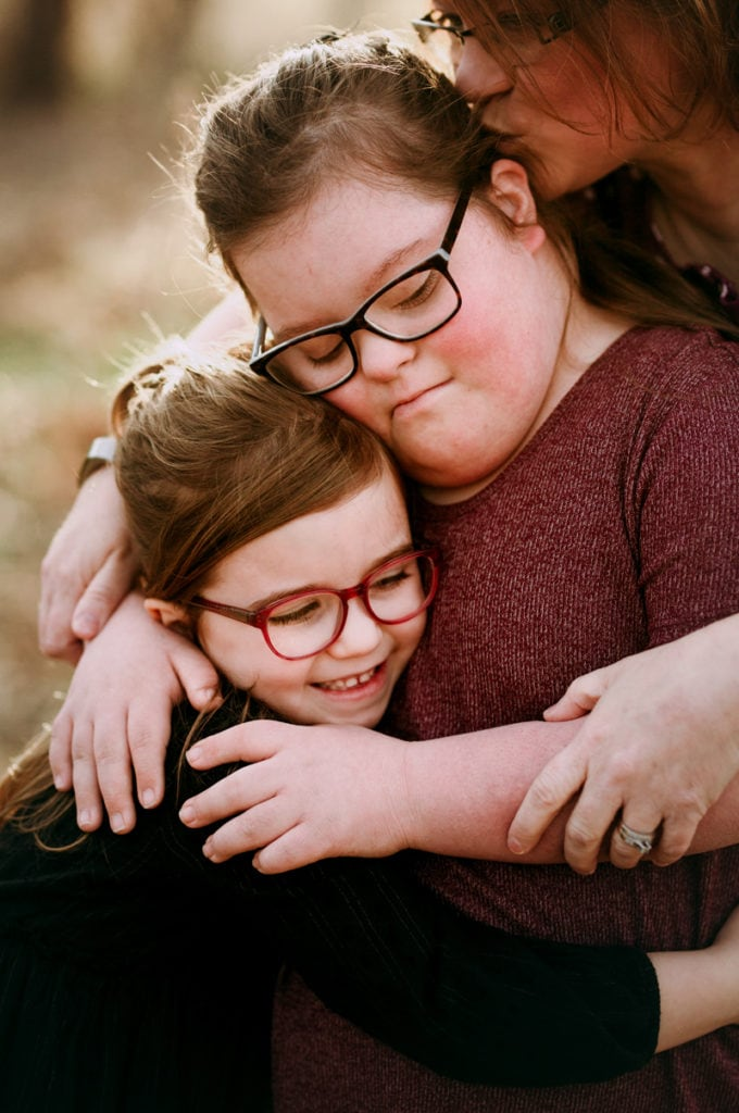 Family Photographer, two sisters embrace warmly, their mother kisses the elder sister on the back of the head lovingly