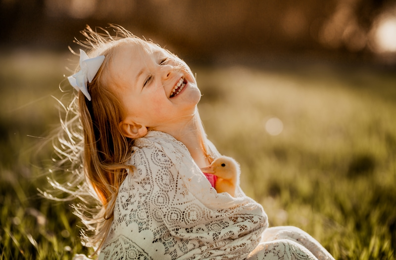 Family Photographer, a young girl wrapped in a lacy throw holds a duck and smiles outdoors in the sunlight